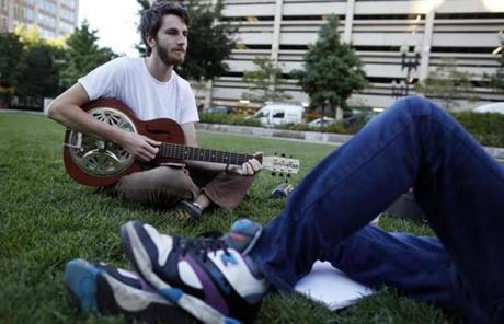Greg Tucker, 23, of Merrimack, N.H., played guitar as he sat with his friend Brian Hoy, 24, of Saugus.